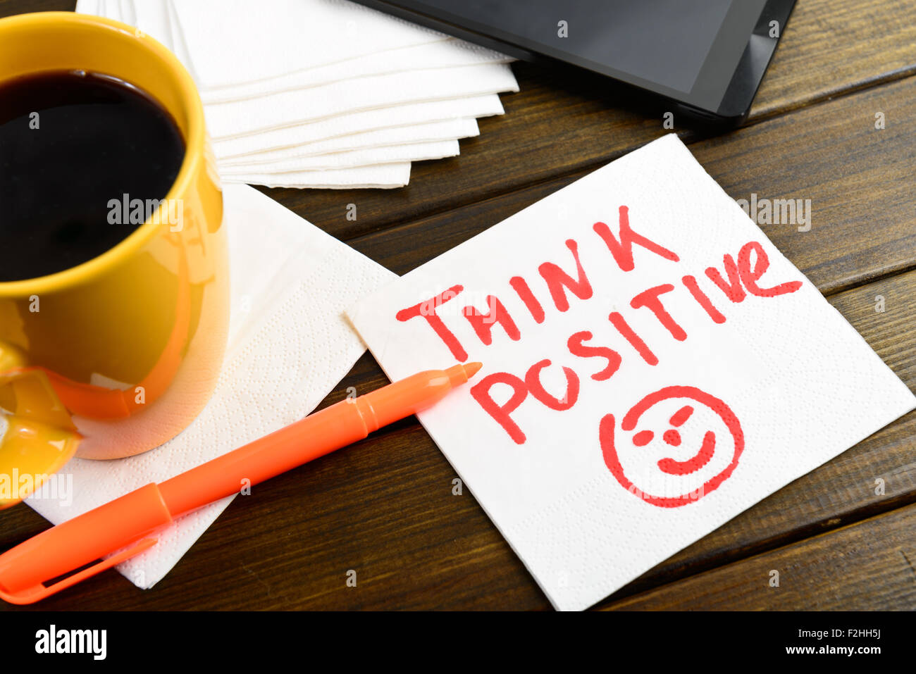 Think positive writing on white napkin around coffee pen and phone on wooden table - Stock Image