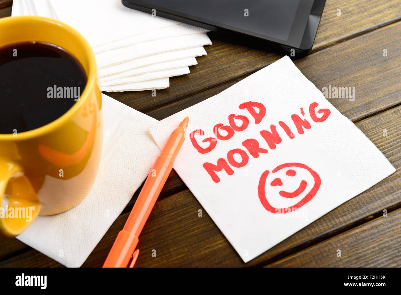 Good morning writing on white napkin around coffee pen and phone on wooden table - Stock Image