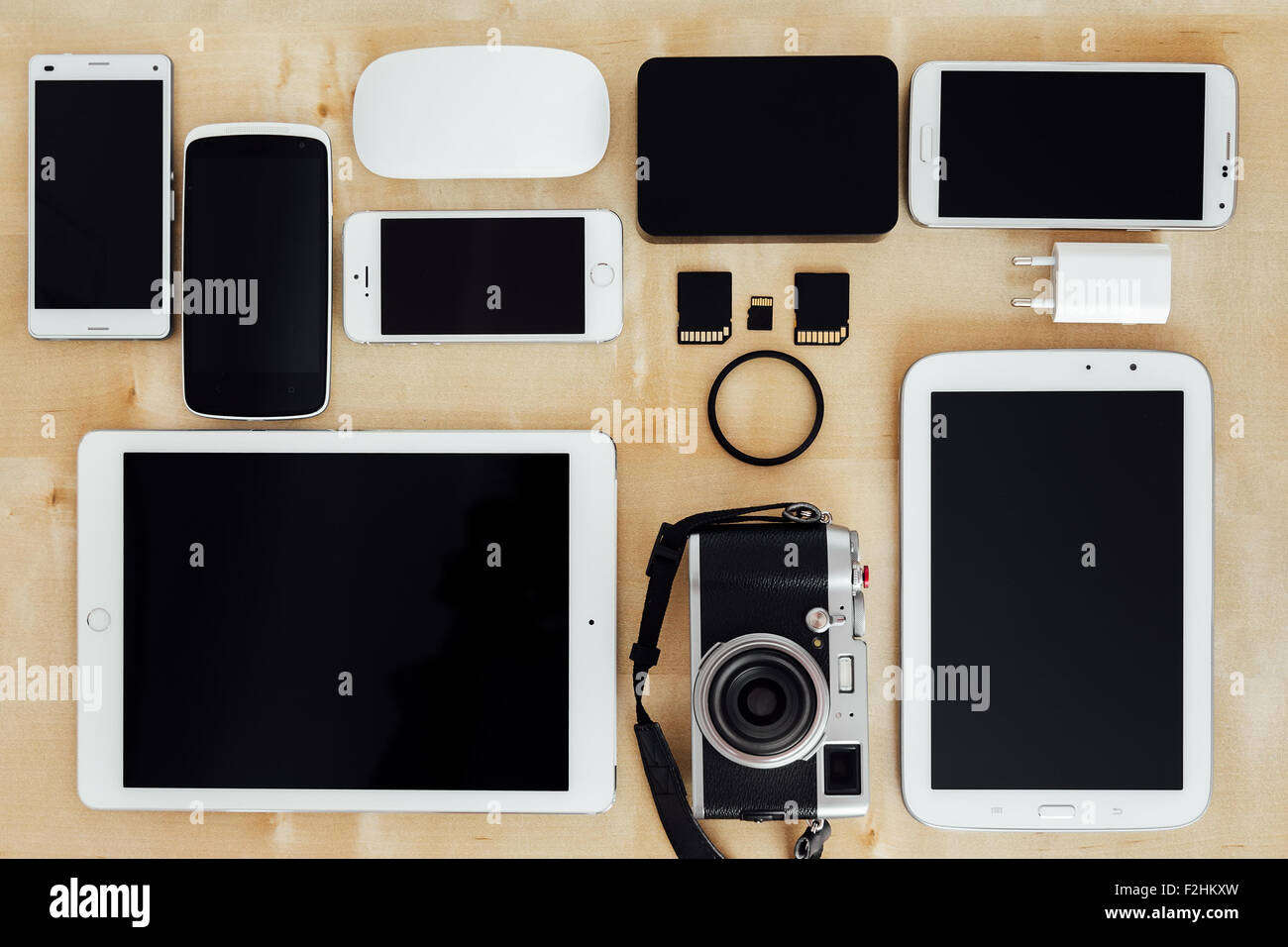 Collection of digital tools of a photographer, with camera, cards, and tablets on a wooden desk - Stock Image