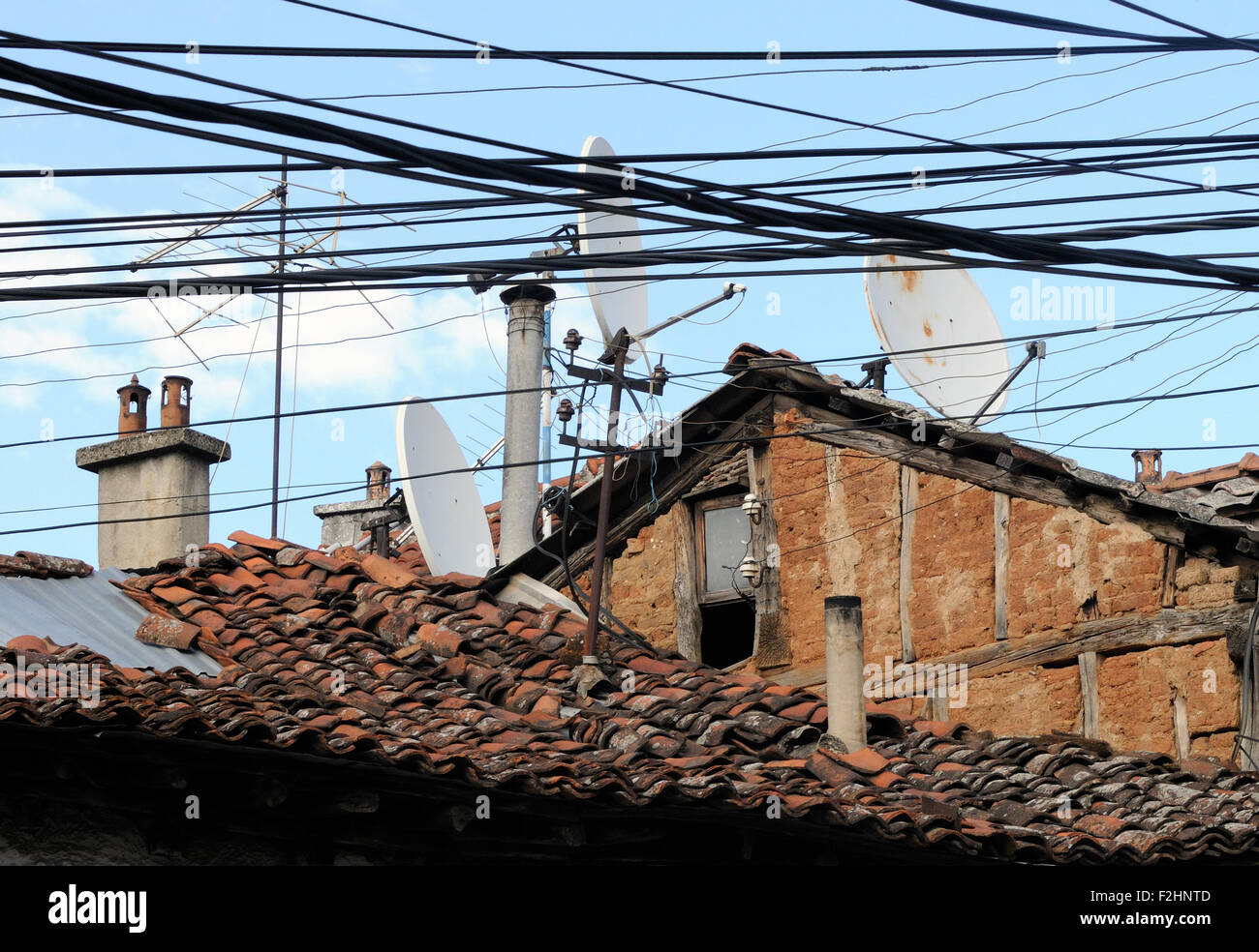 A Tangle Of Electricity And Communications Cables Television Stock Satellite Tv Wiring Aerials Dishes Over Ancient Tiled Roofs In Prizren