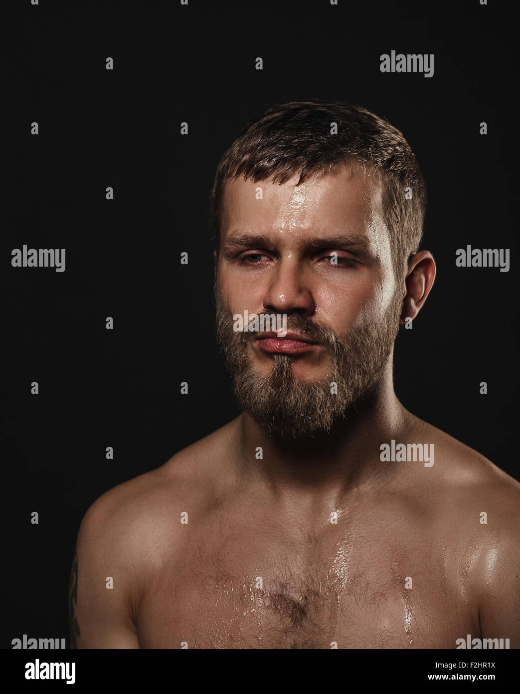 Athletic bearded boxer on a dark background - Stock Image
