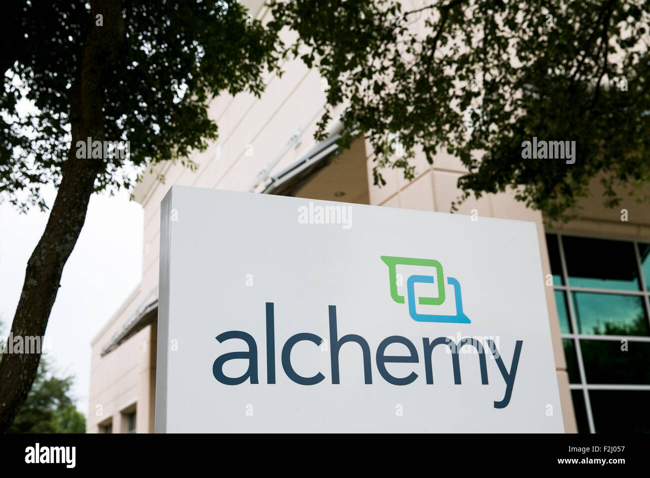 A logo sign outside of the headquarters of Alchemy Systems, LP, in Austin, Texas on September 11, 2015. - Stock Image