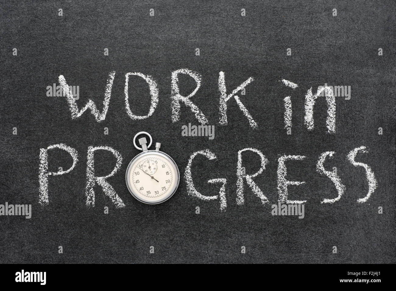 work in progress phrase handwritten on chalkboard with vintage precise stopwatch used instead of O - Stock Image
