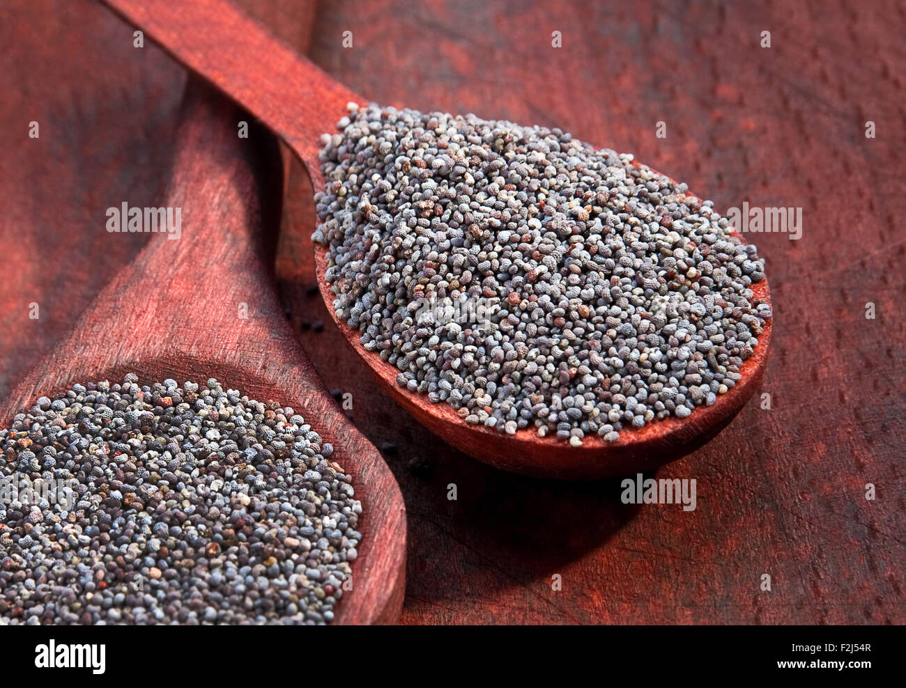Dry poppy seed closeup in wood spoon - Stock Image