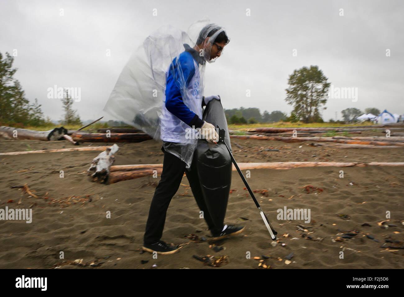 Vancouver, Canada. 19th Sep, 2015. A participant in rain coat collect debris at Iona Beach in Richmond, Canada, - Stock Image
