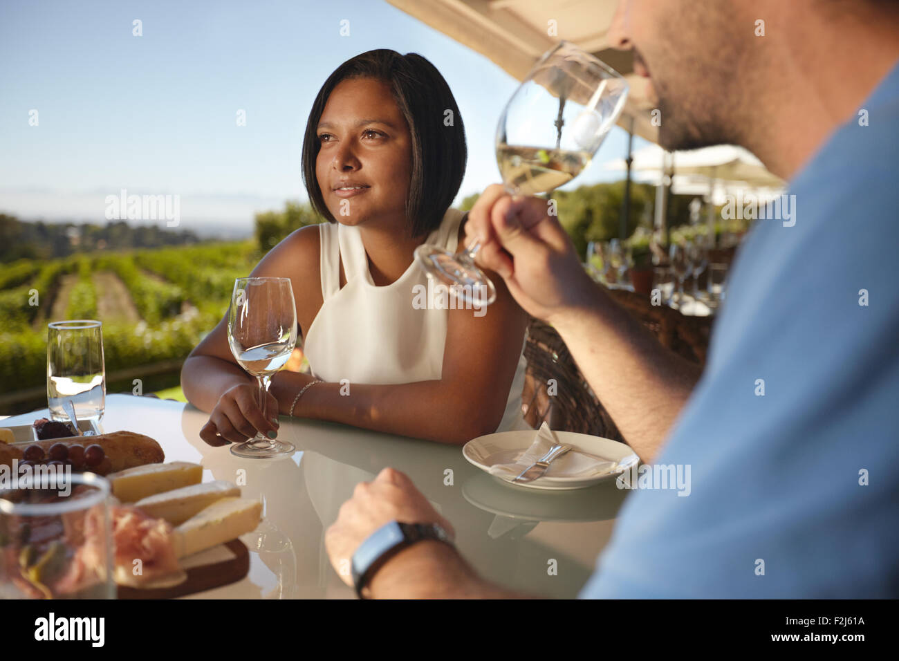Young woman with a man drinking wine. Couple on vacation in outdoor wine bar restaurant by a vineyard. - Stock Image