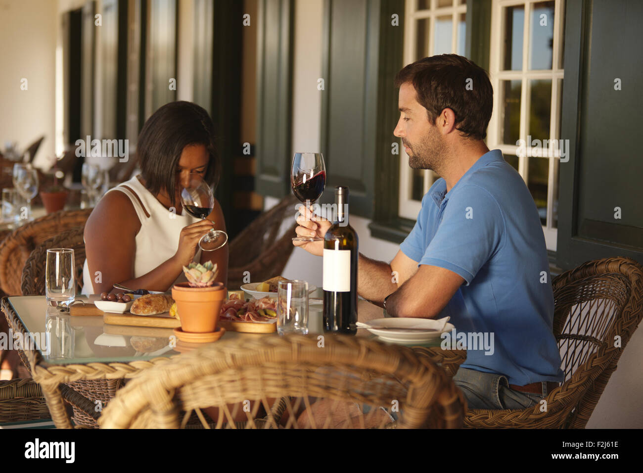 Young couple sitting at table tasting red wine at winery restaurant. Couple at wine tasting with woman smelling - Stock Image
