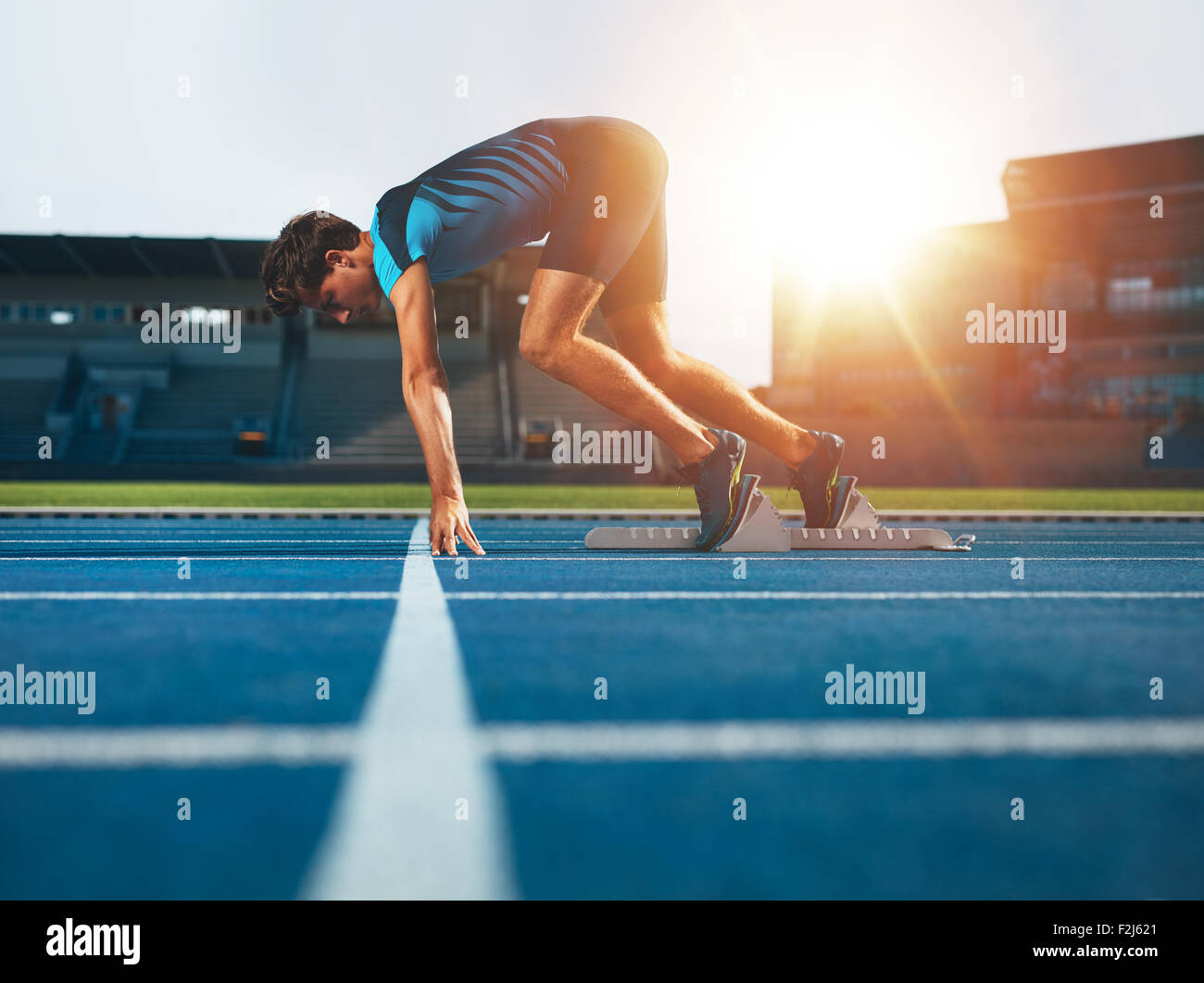Male athlete on starting position at athletics running track. Runner practicing his sprint start in athletics stadium - Stock Image