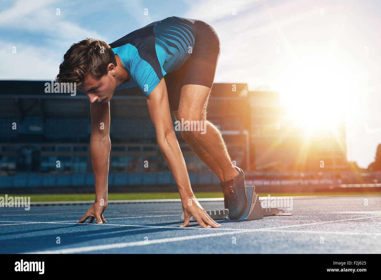 Young male runner taking ready to start position against bright sunlight. Sprinter on starting block of a racetrack - Stock Image
