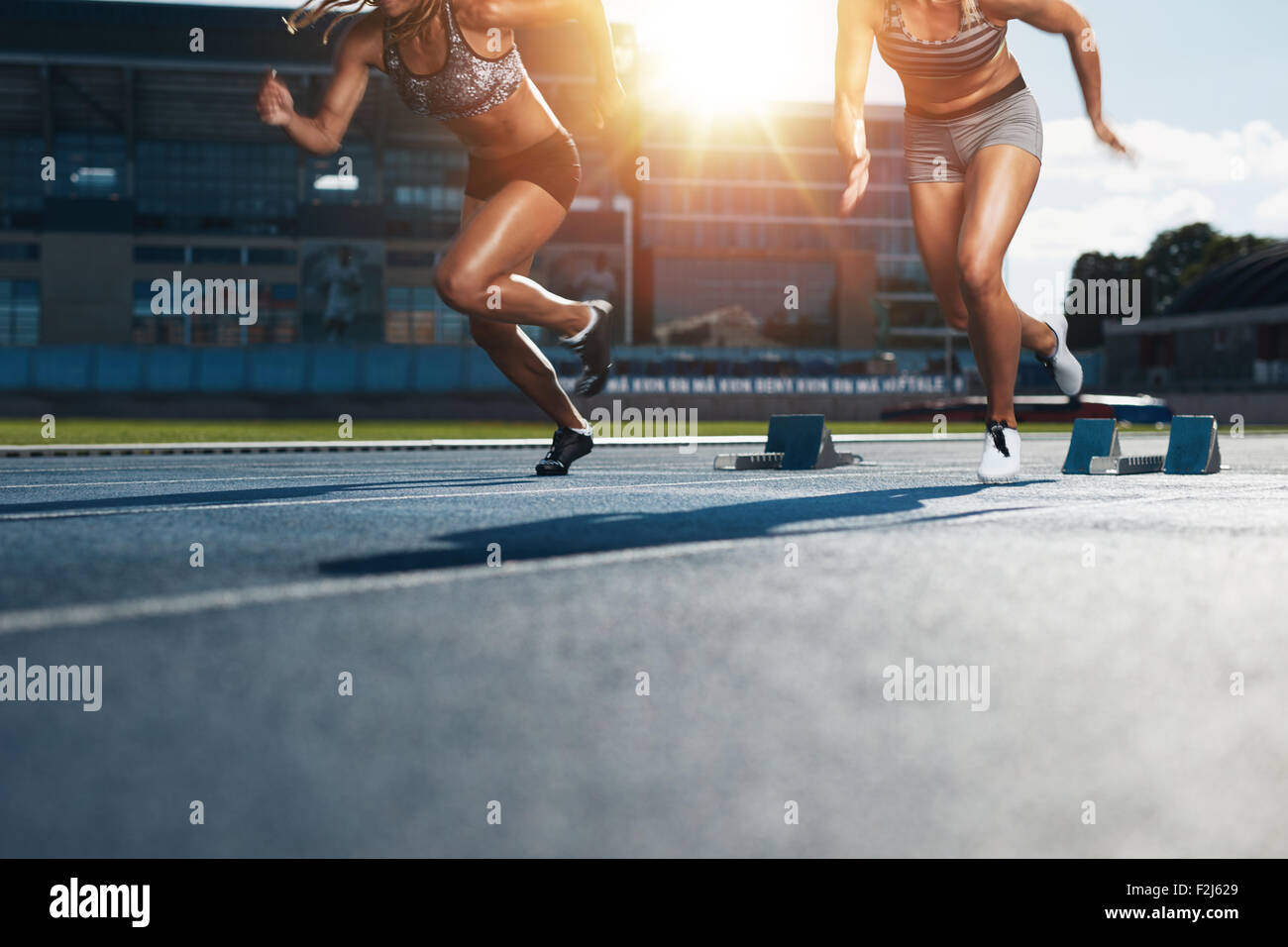 Sprinters starts out of the blocks on athletics racetrack with bright sunlight. Low section shot of female athletes - Stock Image
