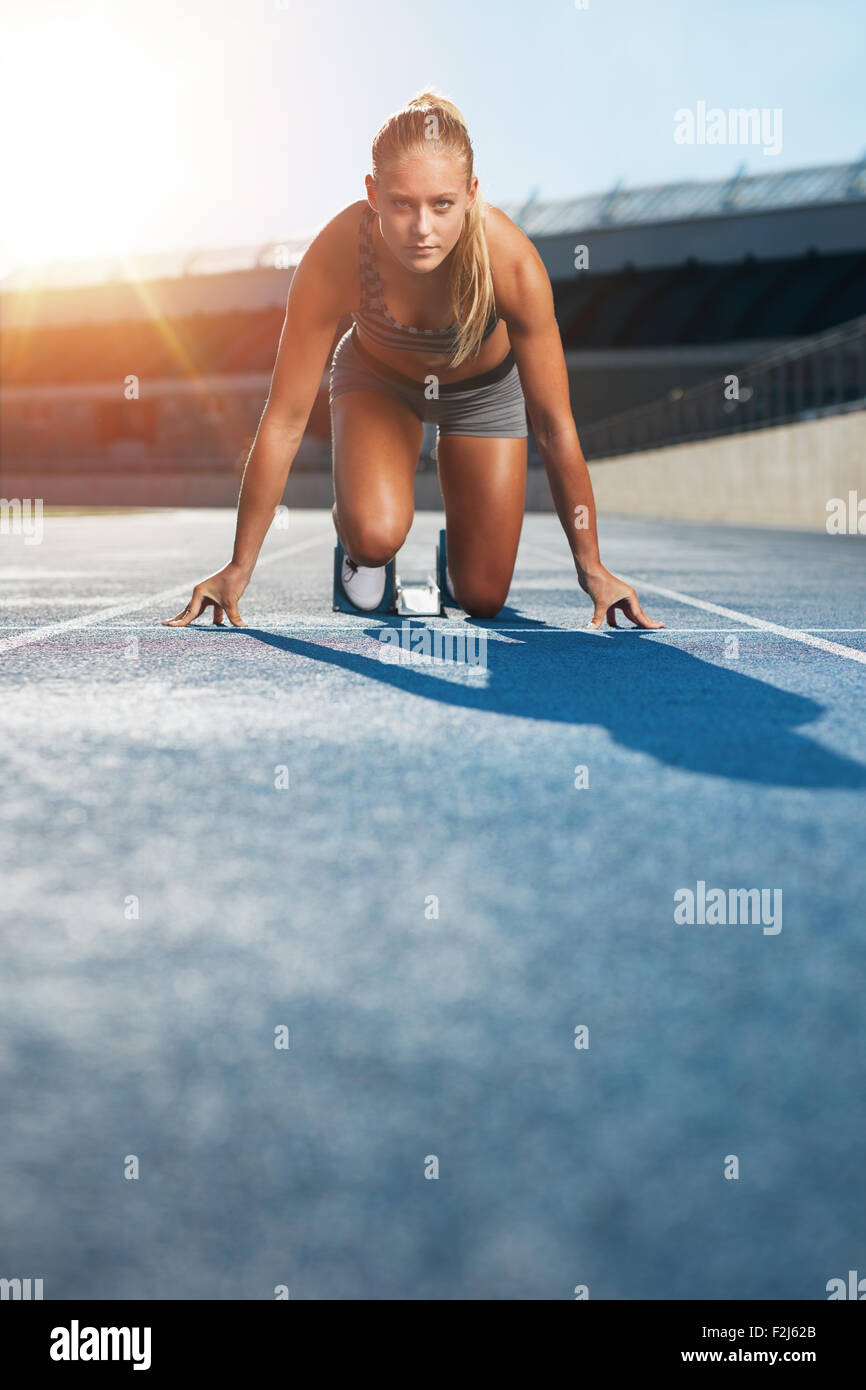 Young woman sprinter in the starter position on a race track at a sports stadium looking up at camera with determination. - Stock Image