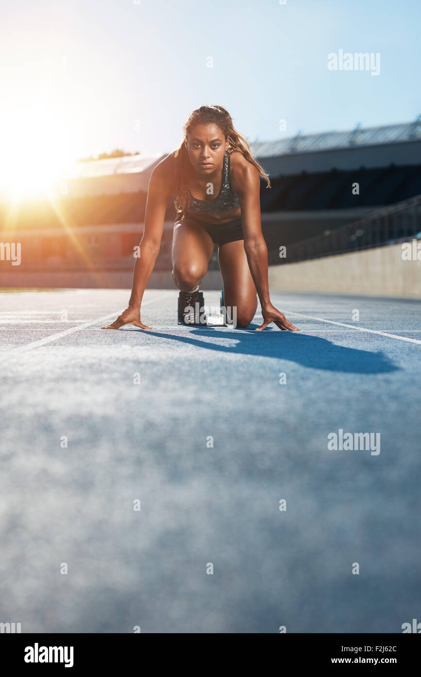 Vertical shot of young female sprinter taking ready to start position facing the camera.  Woman athlete in starting - Stock Image