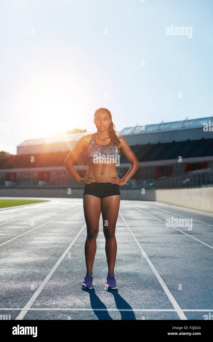 Full length outdoor shot of african young woman on stadium preparing herself for a run. Professional female athlete - Stock Image