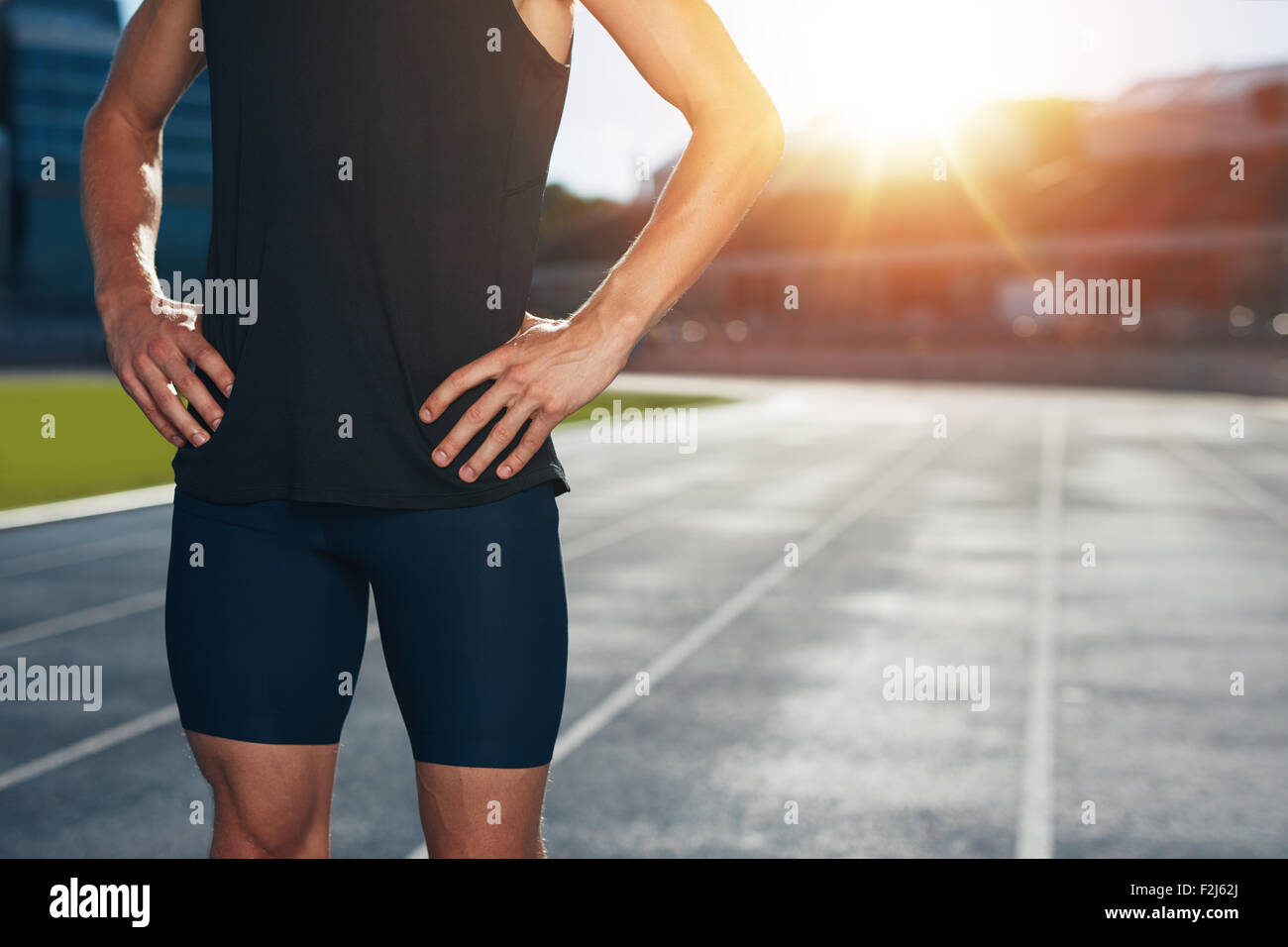 Mid section shot of male athlete standing on race track with his hands on hips on a bright sunlight. Cropped shot - Stock Image