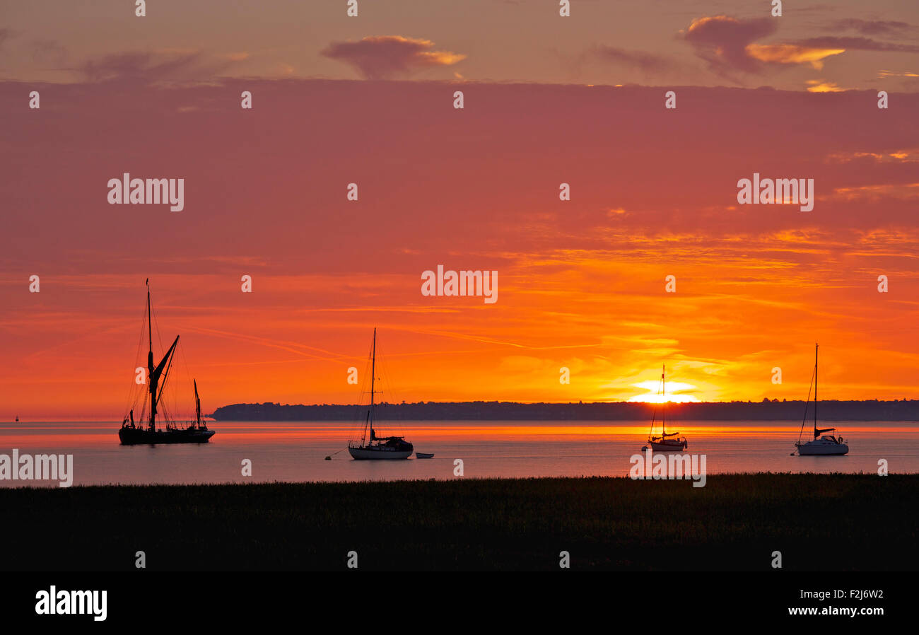 Swale Estuary, Kent, UK. 20th September 2015. UK Weather. Sunrise brings a glorious red sky over boats moored in - Stock Image