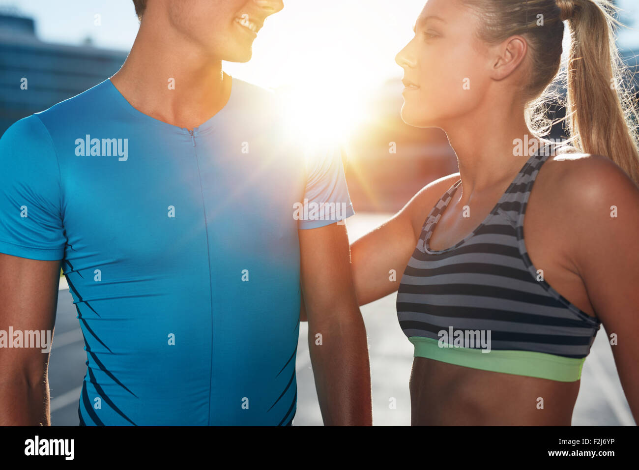 Closeup shot of two young athletes standing on stadium race track on a bright sunny day. Man and woman in sports - Stock Image