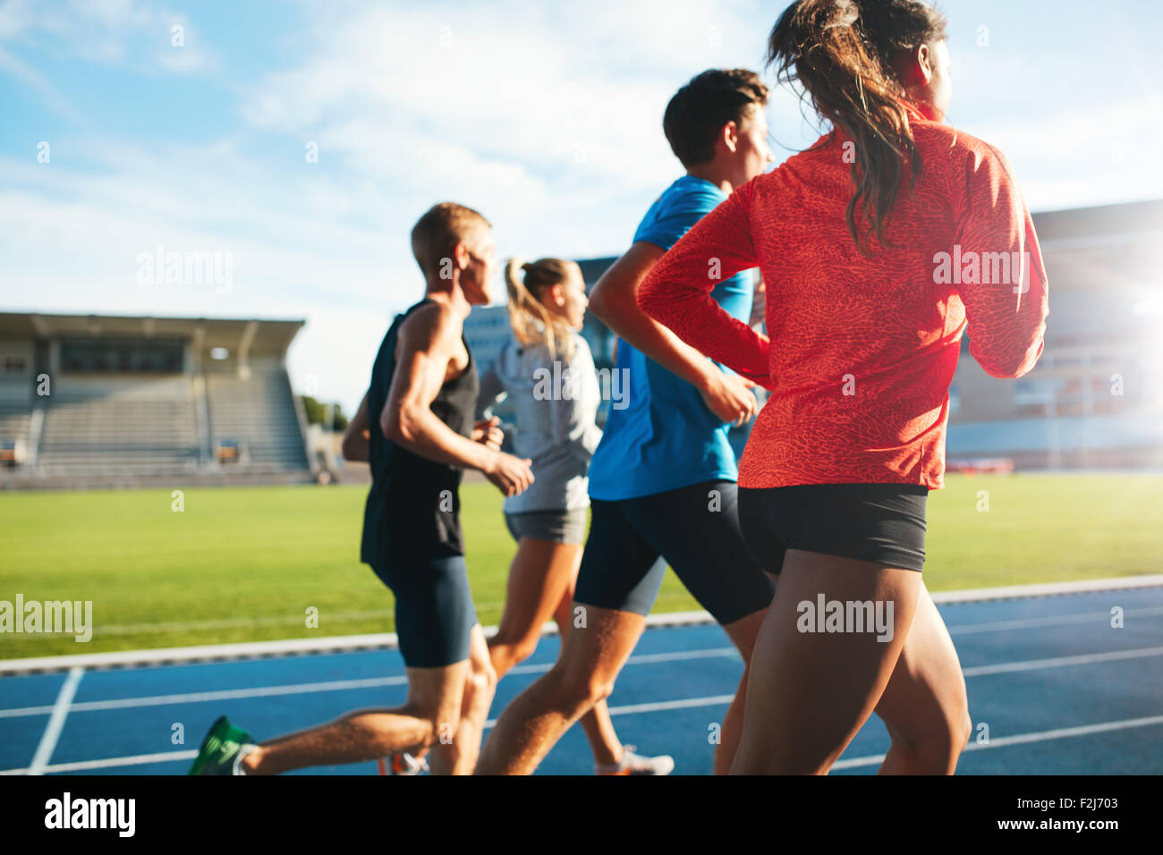 Rear view of young people running together on race track. Young athletes practicing a run on athletics stadium track. - Stock Image