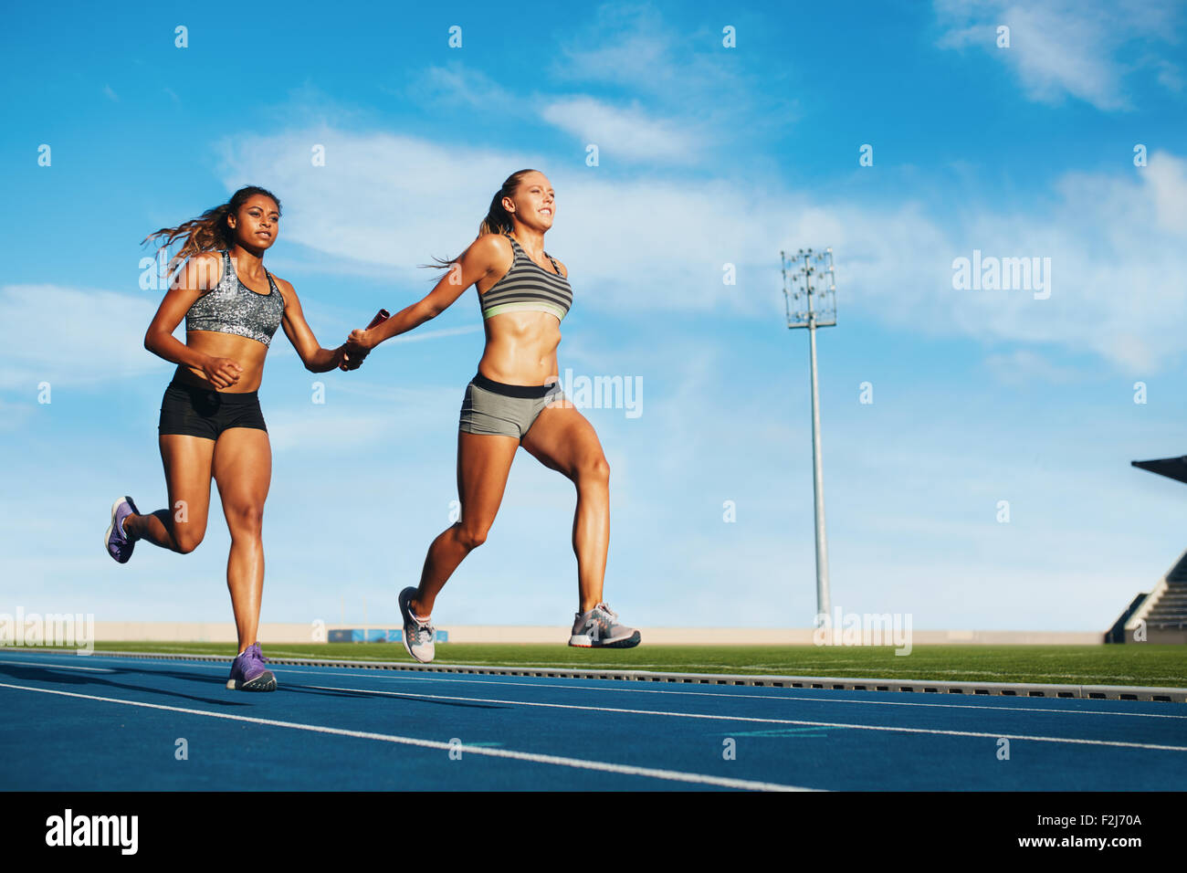 Young woman running a relay race and giving relay baton to her teammate. Female runner passing the relay baton during - Stock Image