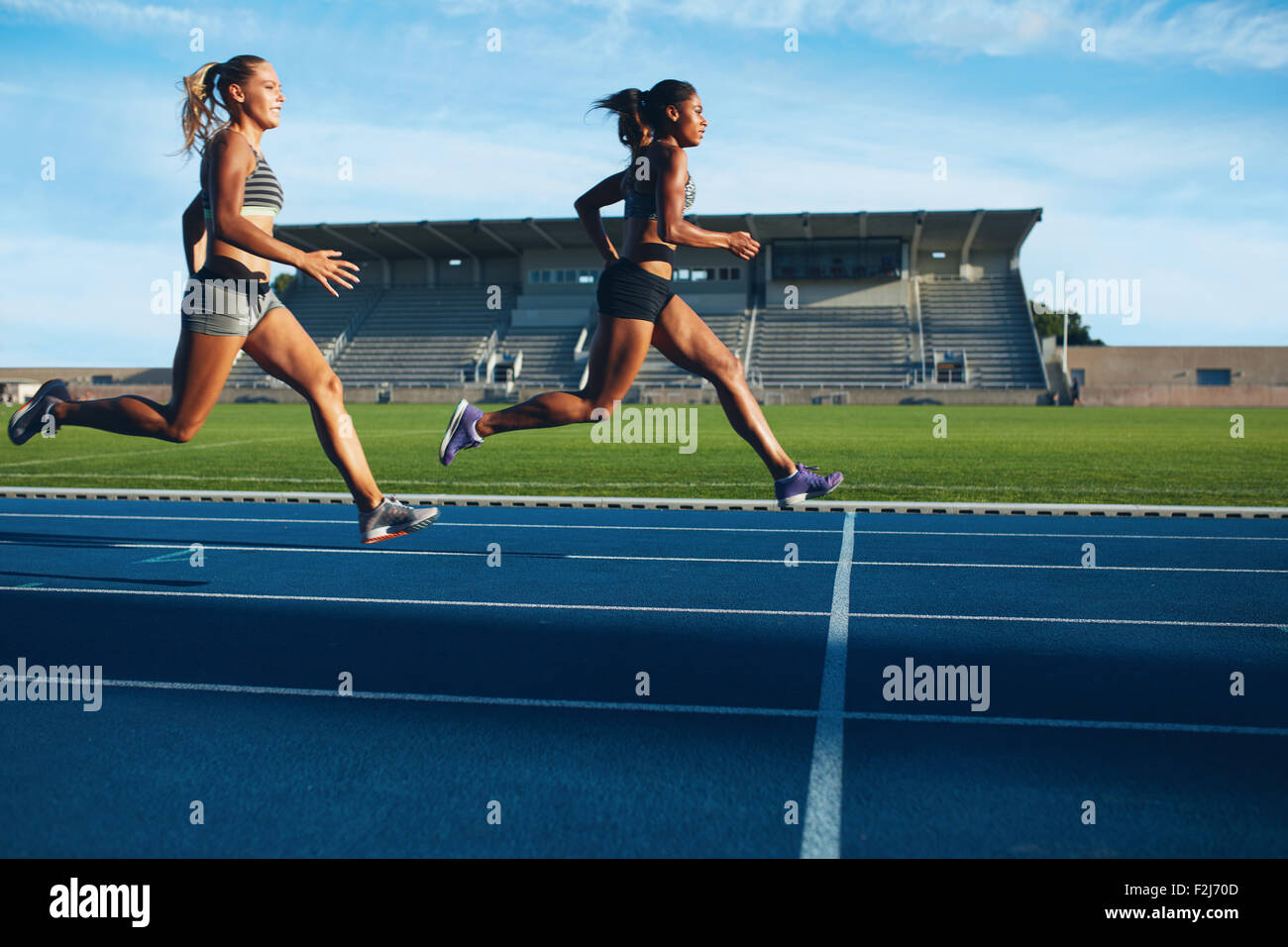 Athletes arrives at finish line on racetrack during training session. Young females competing in a track event. - Stock Image