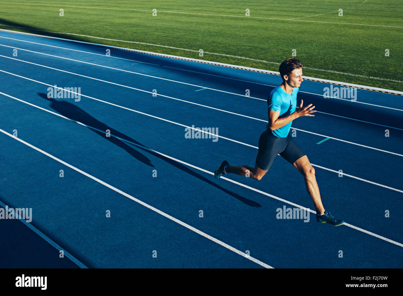 Shot of a young male athlete training on a race track. Sprinter running on athletics tracks. - Stock Image