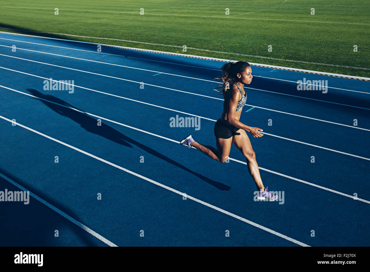 Outdoor shot of young African woman athlete running on racetrack. Professional sportswoman during running training - Stock Image