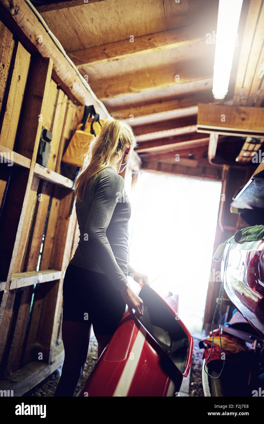 Athletic woman carrying a kayak from the boathouse - Stock Image