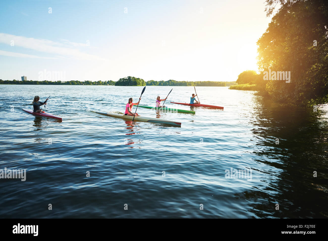 Team of sports kayaks racing on the lake - Stock Image