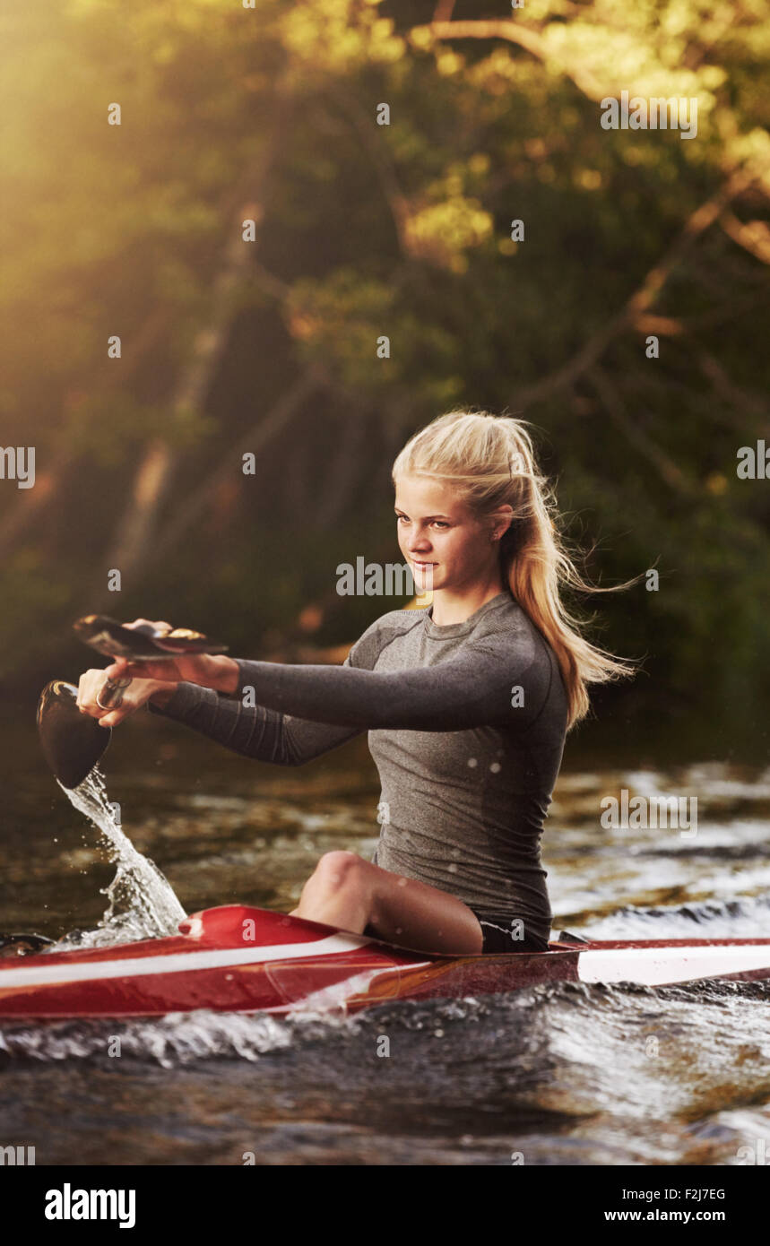 Athletic elite kayaker racing on the water - Stock Image
