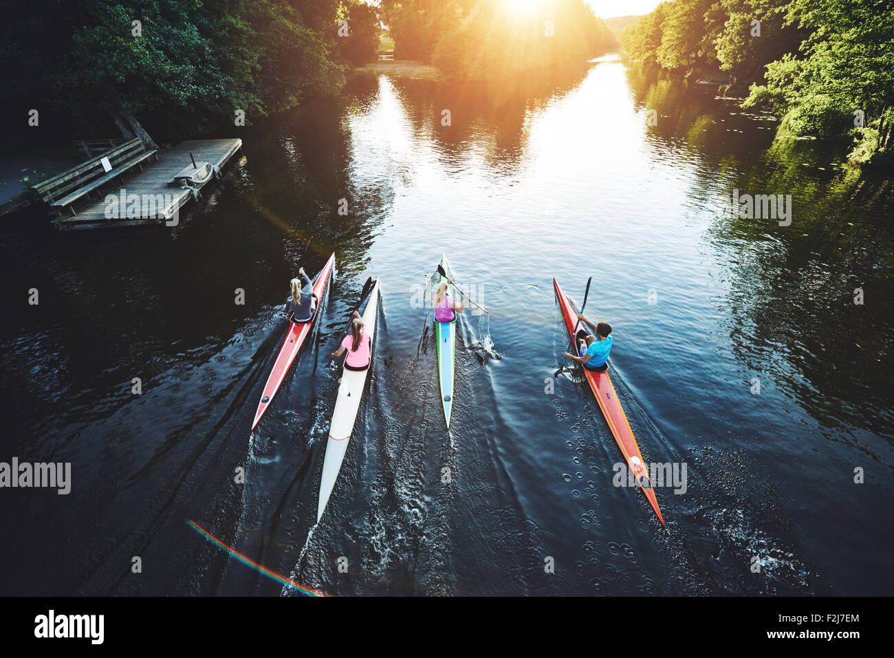 Team of rowing people racing in the sunset - Stock Image