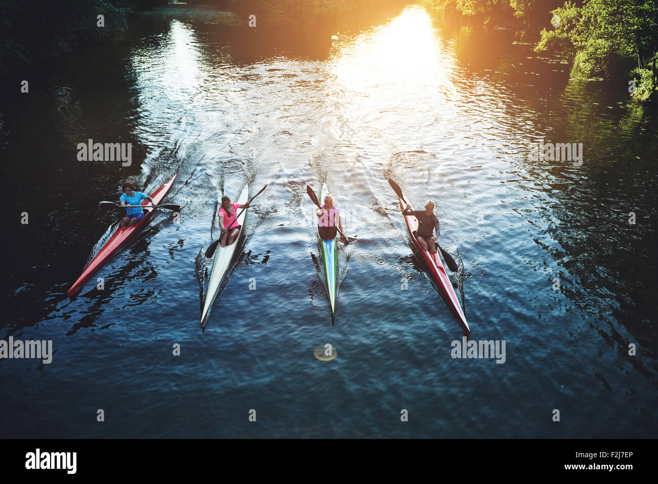 Team of rowing people sailing against camera in sunset - Stock Image