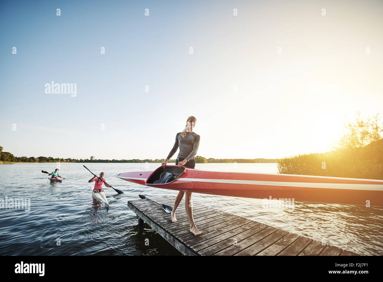 Rowing team after training getting out of the water Stock Photo