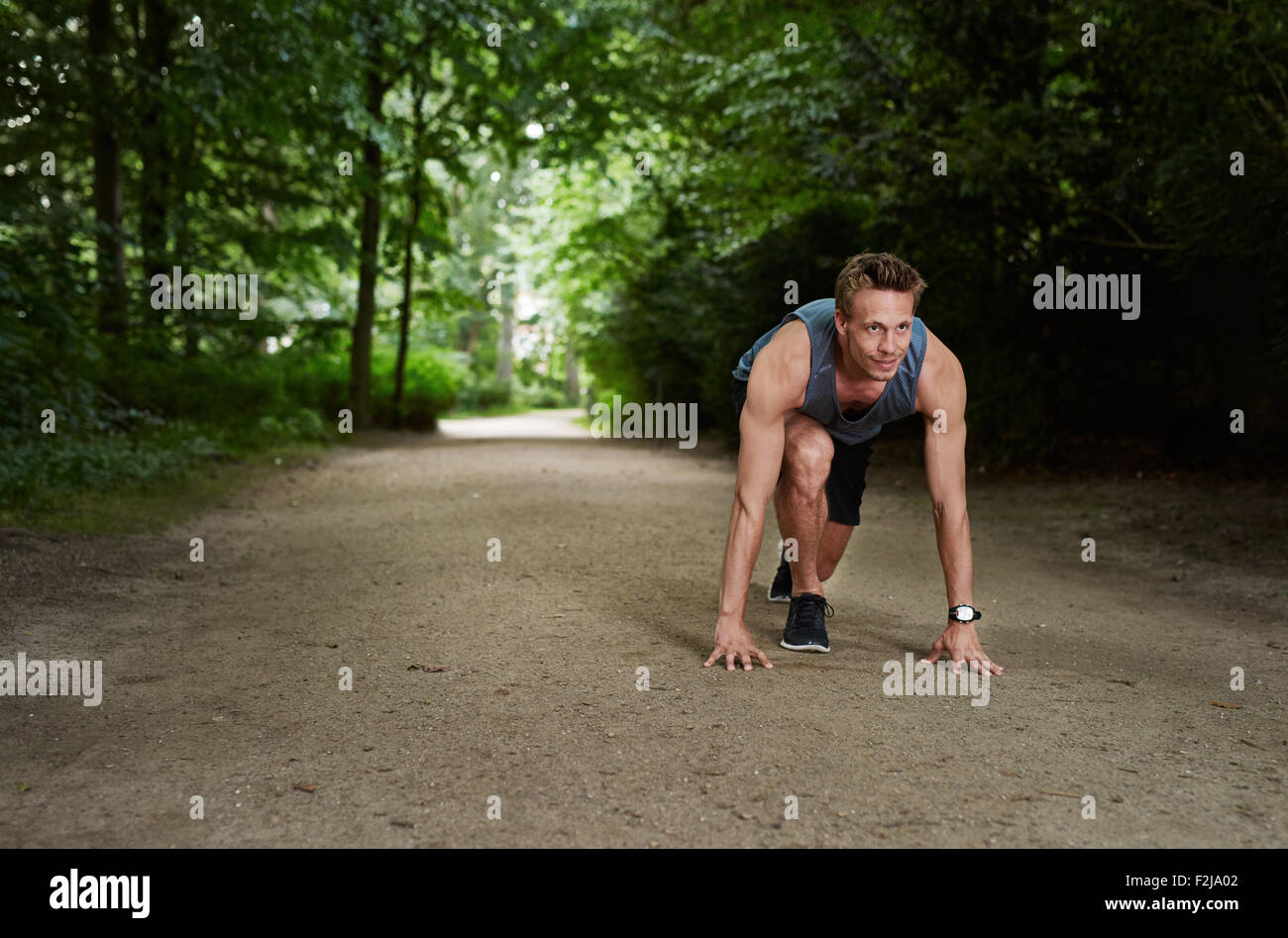 Handsome Athletic Man in Running Start Position and Looking Into the Distance at the Park - Stock Image