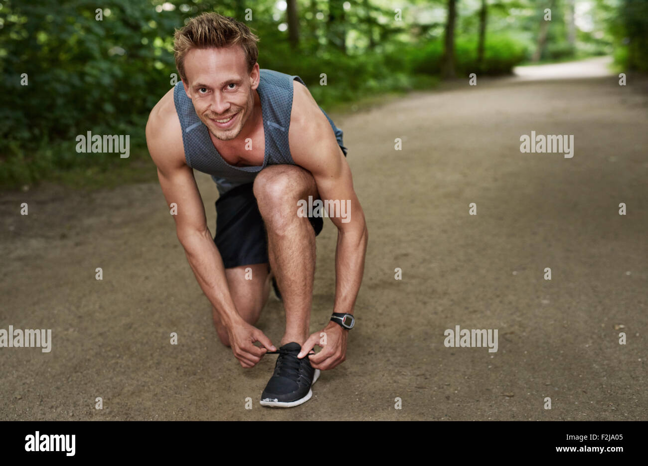 Healthy Muscular Man Smiling at the Camera While Fixing his Shoelace at the Park. - Stock Image