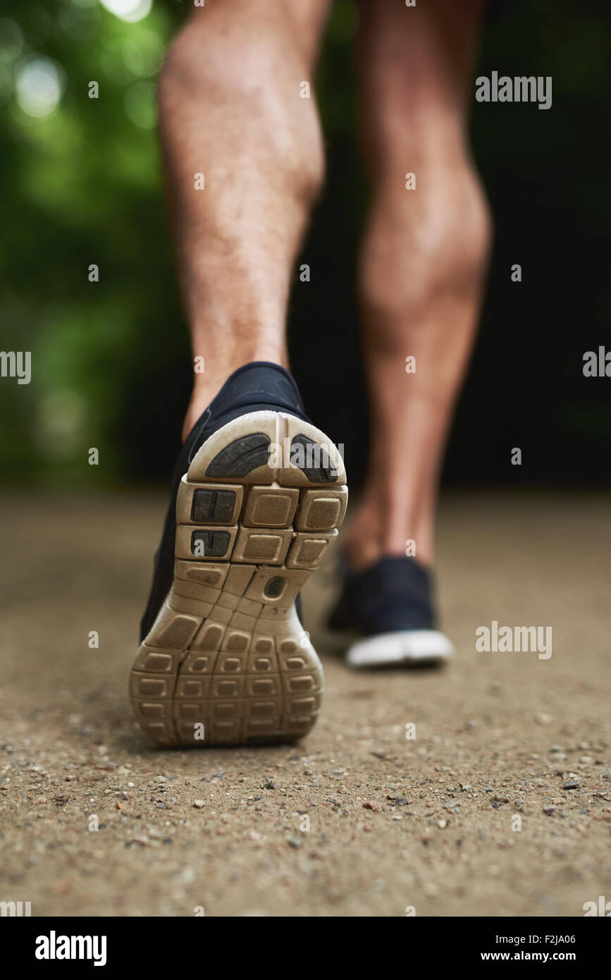 Close up Shoe Sole of an Athletic Young Man Running at the Park - Stock Image