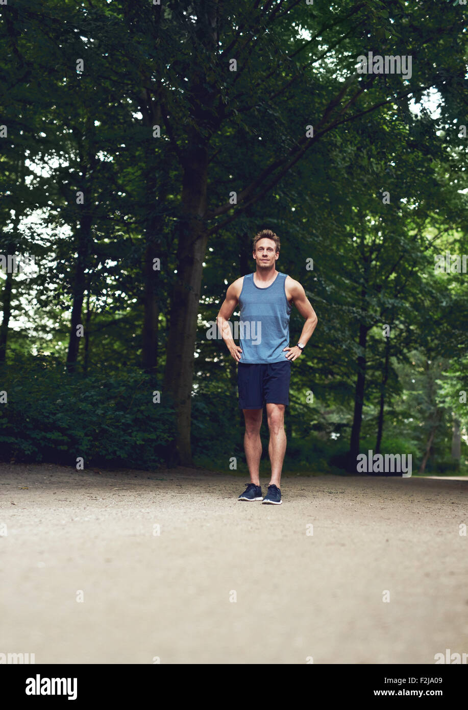 Athletic Young Man Standing at the Park with Hands Holding his Waist and Looking Into the Distance. - Stock Image