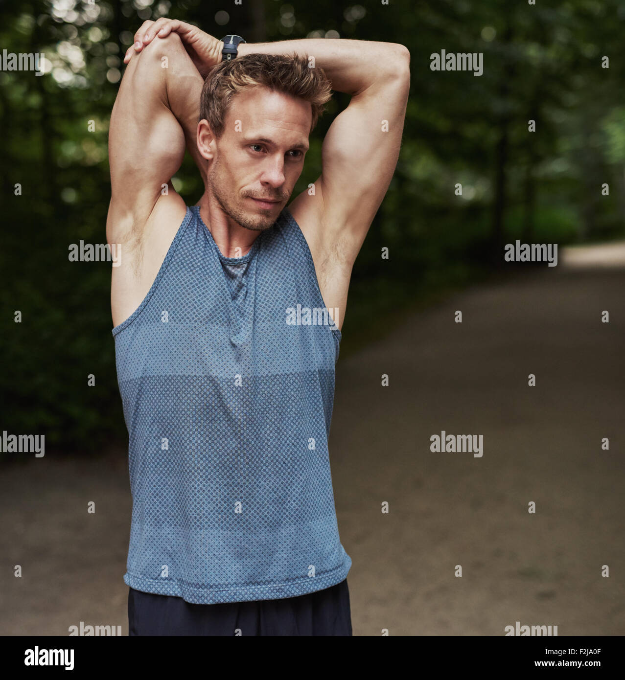 Half Body Shot of a Handsome Athletic Man Stretching his Arms Behind his Head at the Park. - Stock Image