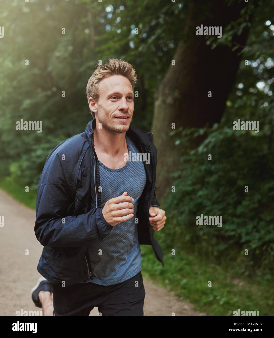 Three Quarter Shot of a Physical Fit Man Running at the Park Early in the Morning with Happy Facial Expression. - Stock Image