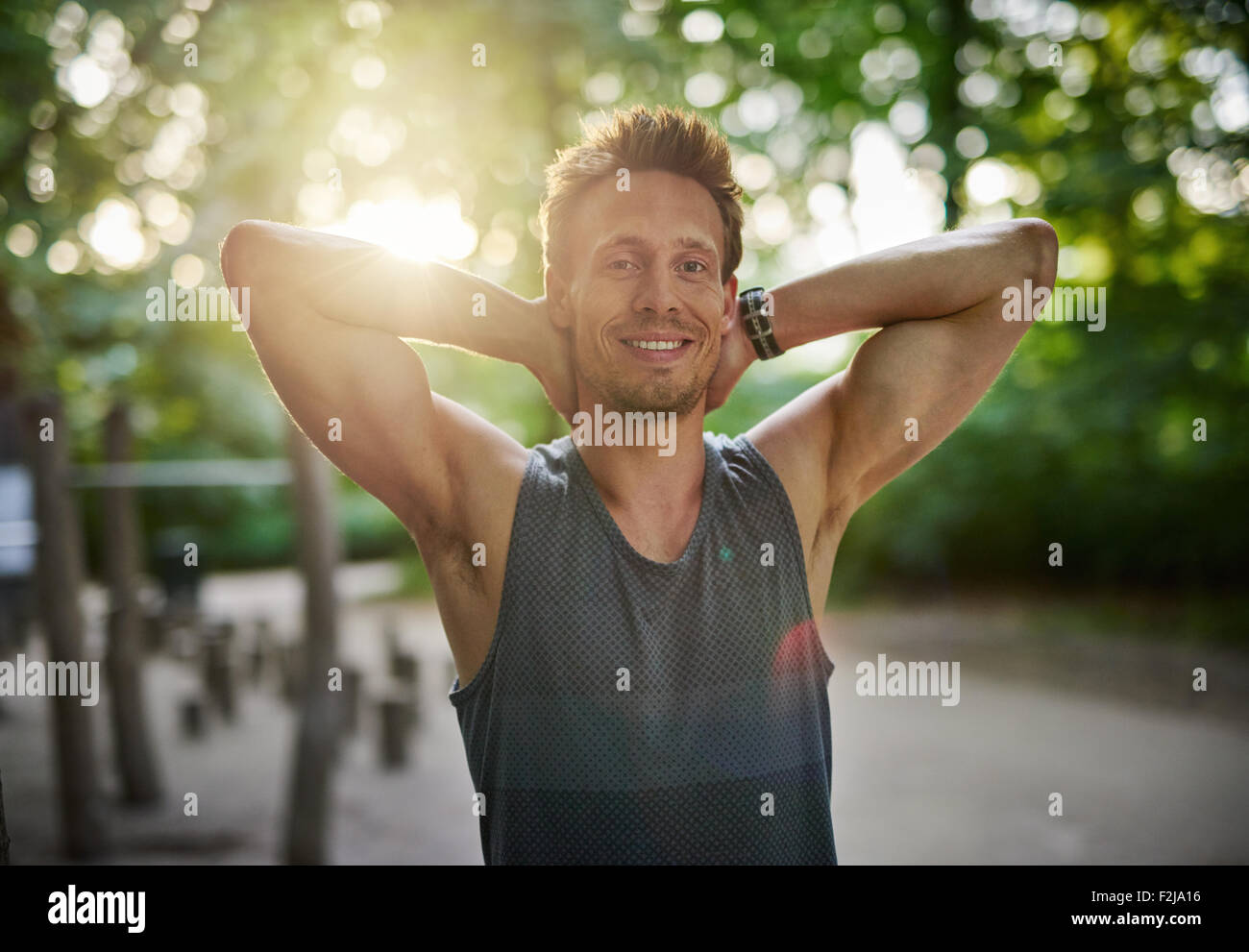 Half Body Shot of an Athletic Young Man at the Park Smiling at the Camera with Hands Behind his Head. - Stock Image