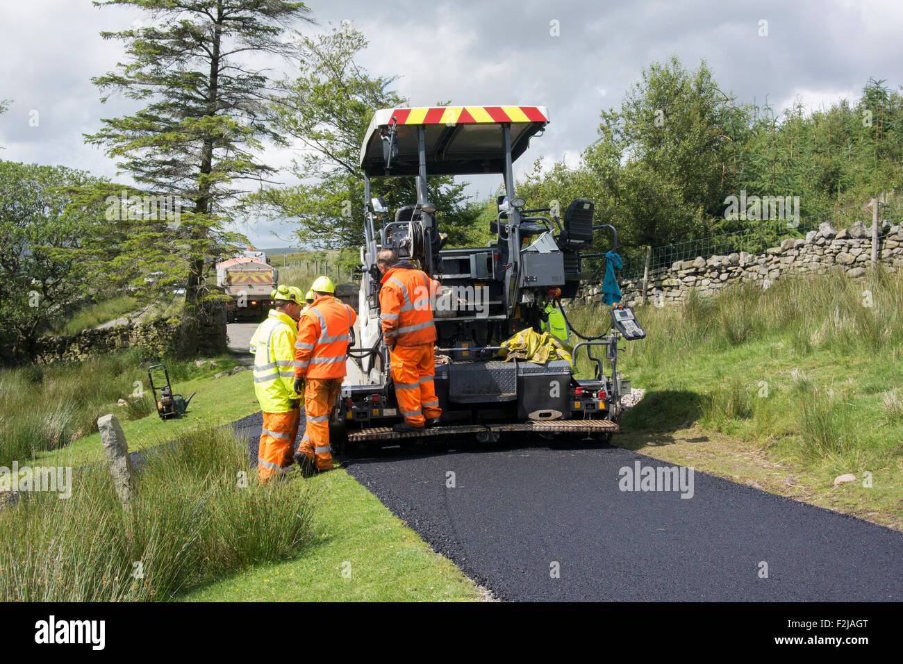 County Council workers laying tarmac on rural road in Cumbria, UK. - Stock Image
