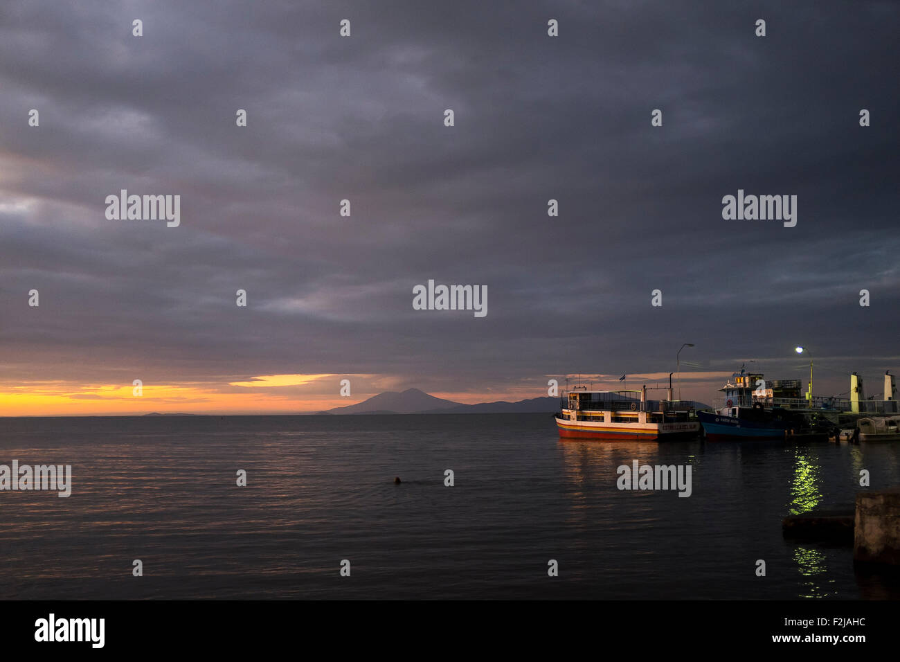 A beautiful and colorful sunset across the ferry dock of Moyogalpa, Ometepe Nicaragua with a dramatic sky - Stock Image