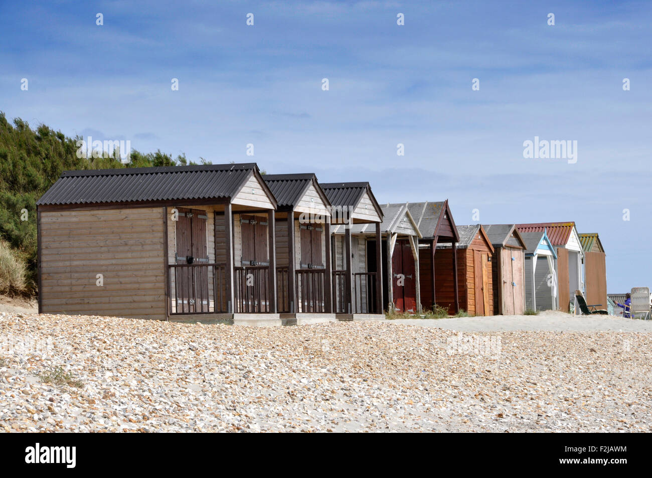 Summer sunlight - bright blue sky - at the beach - wooden beach huts - dreary and dull - contrast - scope for renovation - Stock Image