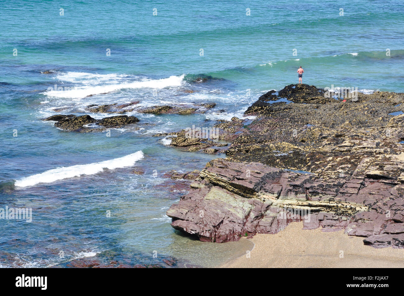 Solitary bather - tiny figure perched on rocks above the sea - breaking waves - blue sea - bright sunshine - Stock Image