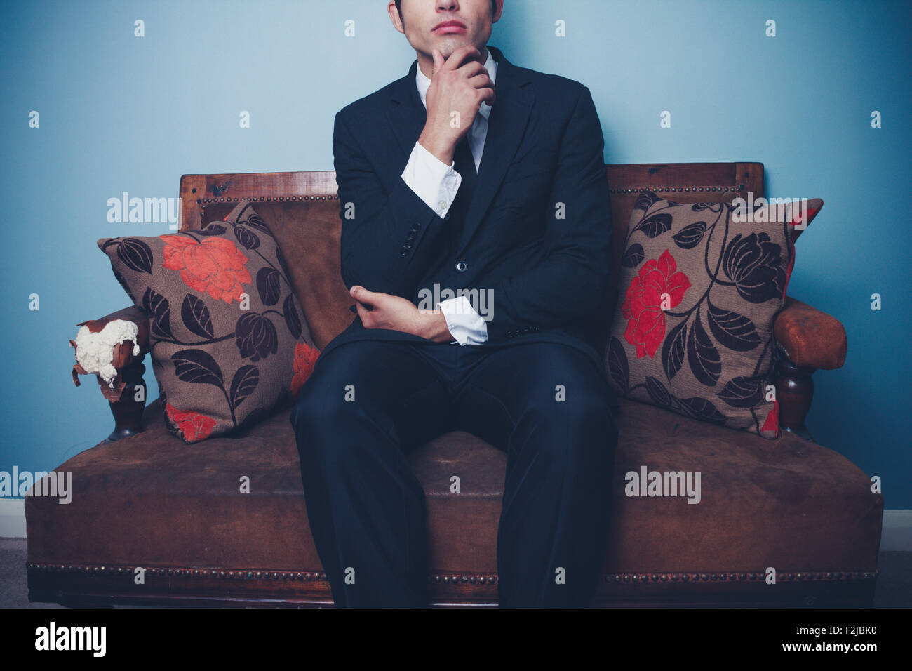 Thoughtful young businessman sitting on sofa - Stock Image