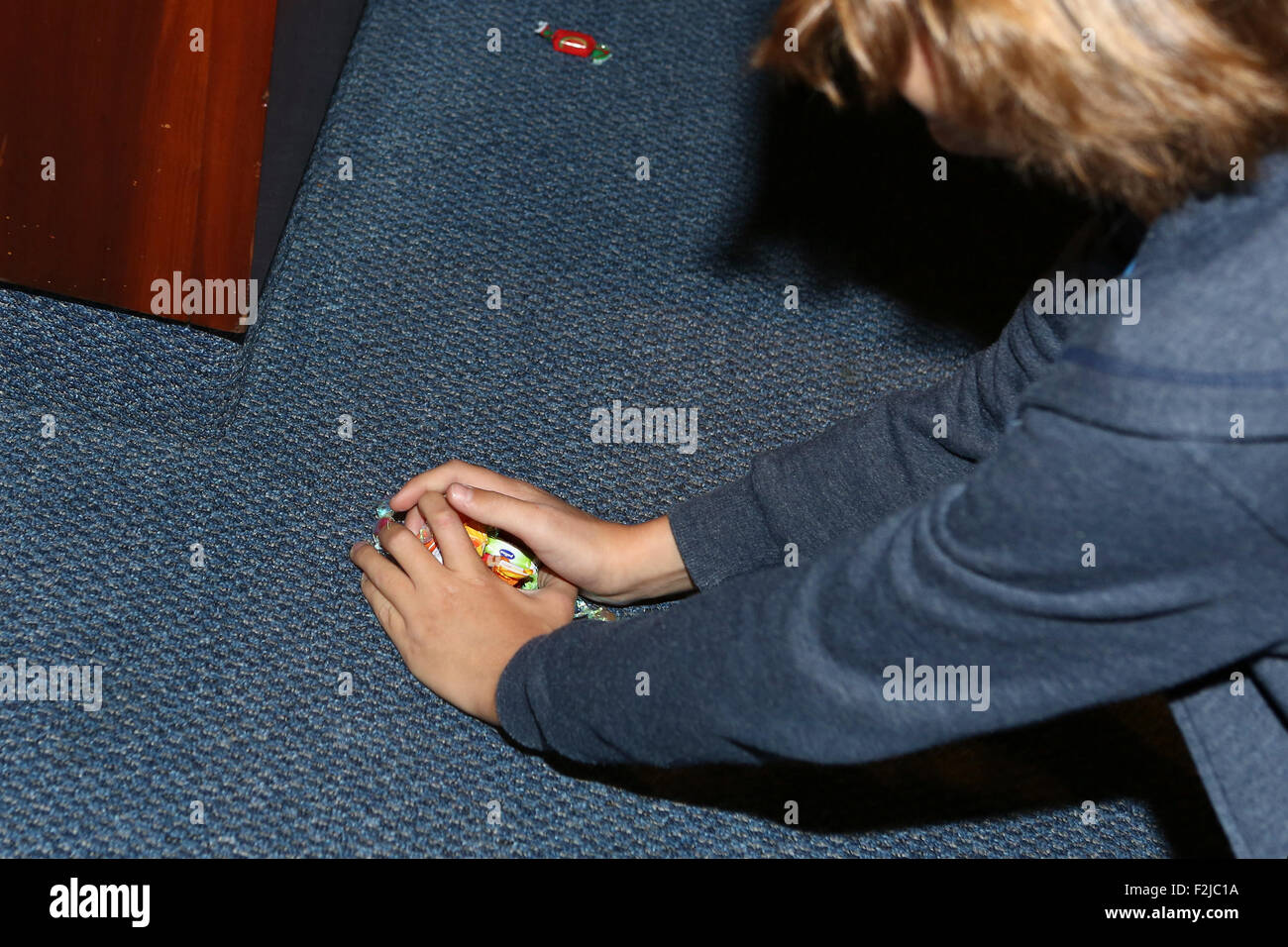 Boy collects sweets that were thrown at the Bar Mitzvah boy for good luck - Stock Image