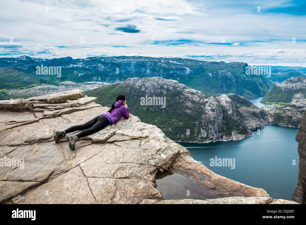 Woman looking at the landscape from a height. Beautiful Nature Norway Preikestolen or Prekestolen. - Stock Image