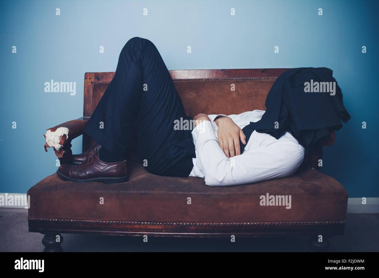 Young businessman on sofa sleeping - Stock Image