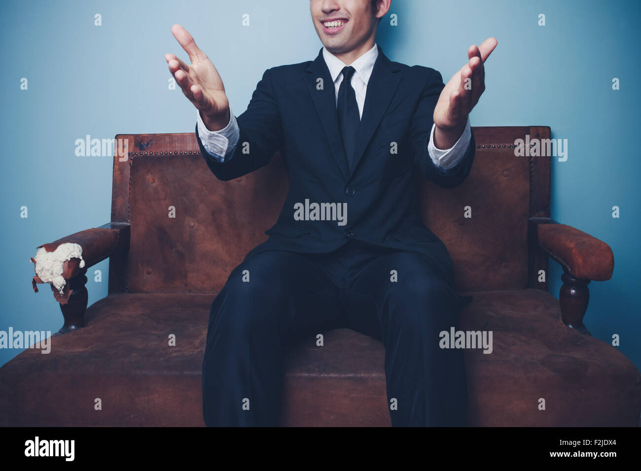 happy young businessman sitting on an old sofa - Stock Image