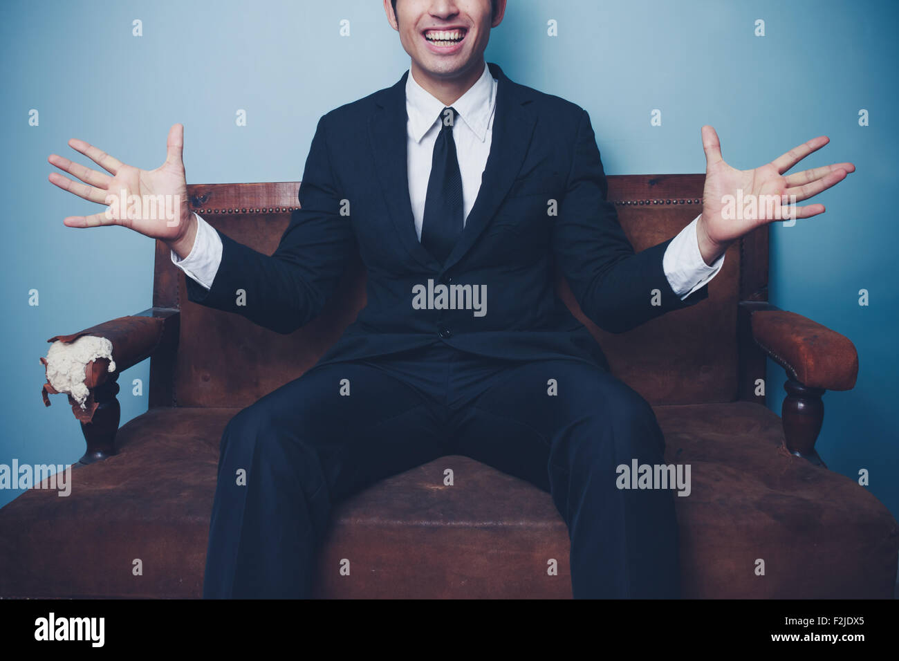 Happy young businessman sitting on sofa - Stock Image