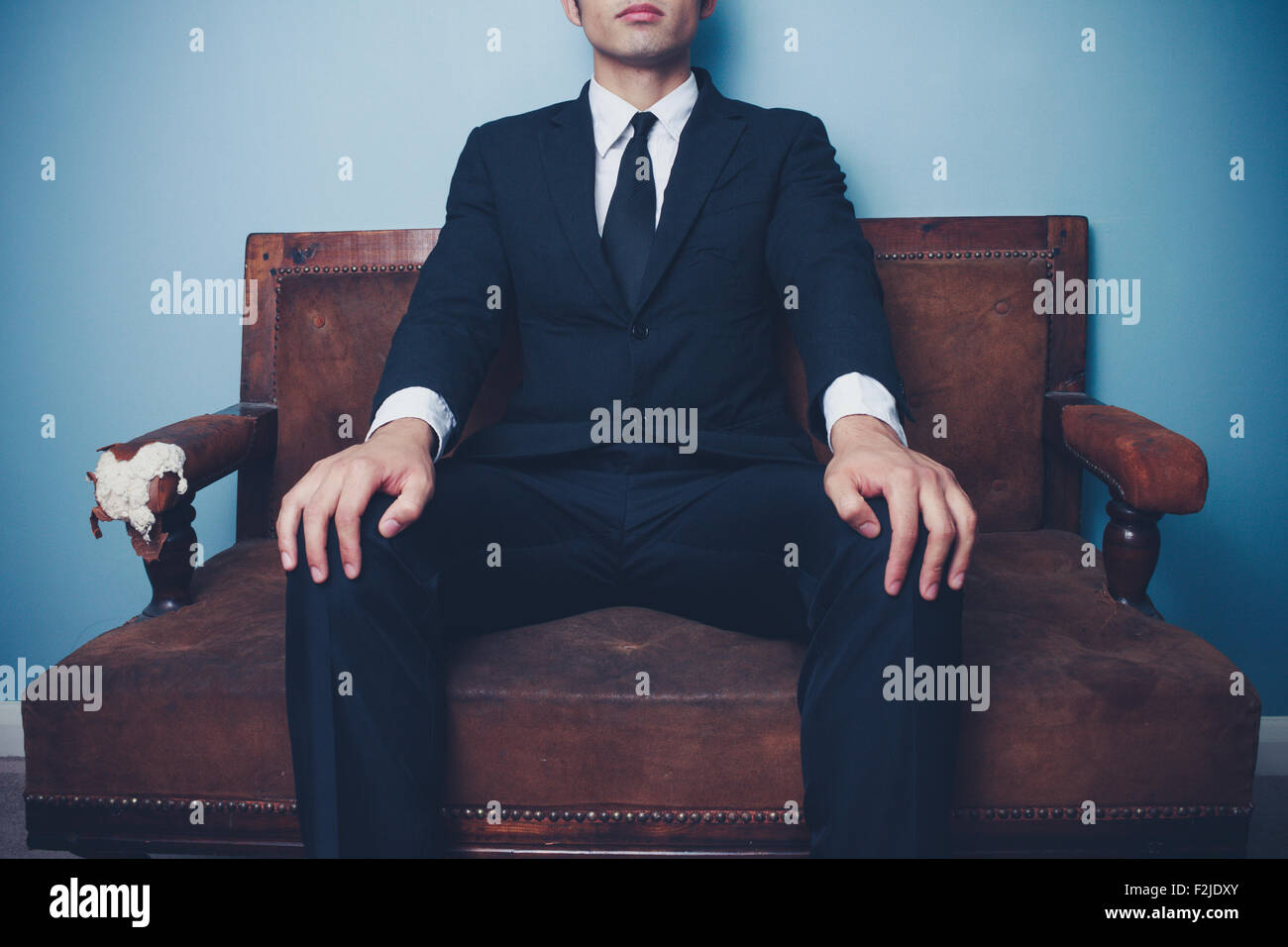 Young businessman sitting on sofa - Stock Image