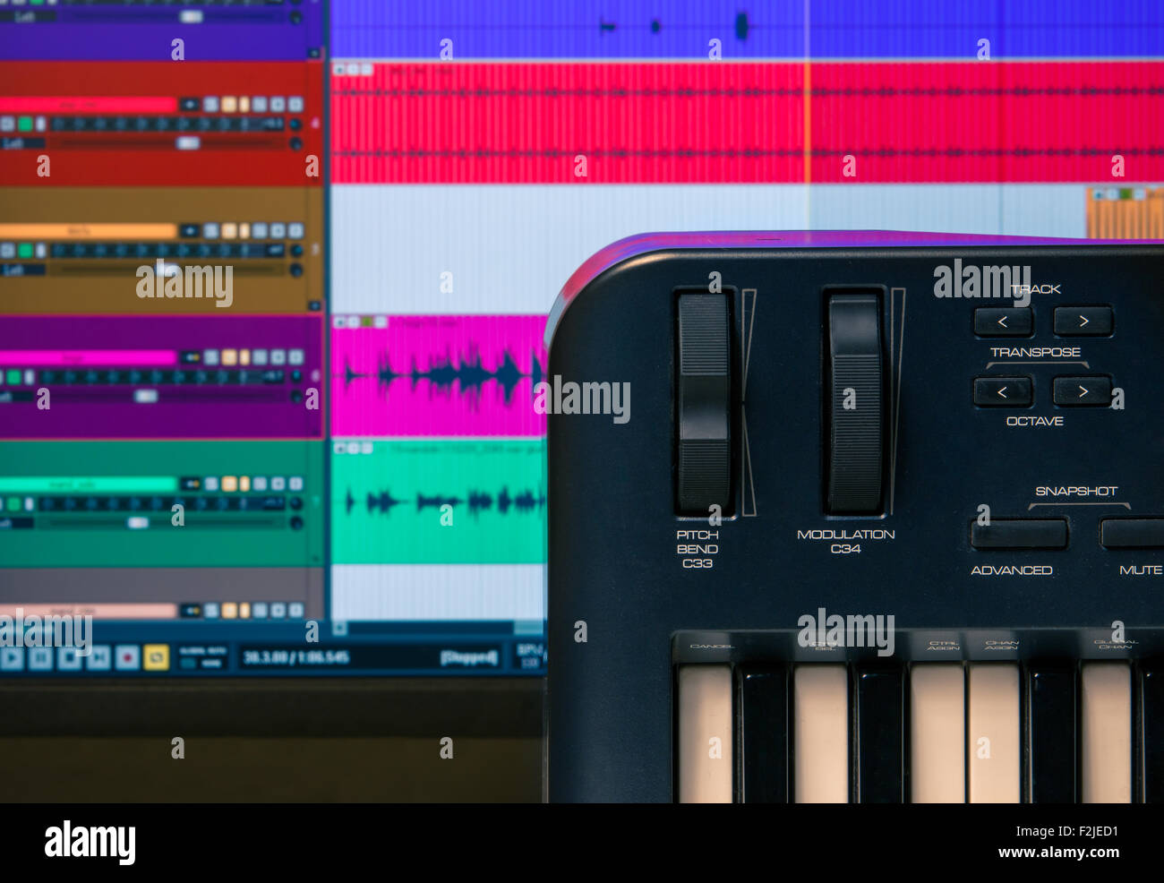 Midi keyboard and controller with faders and buttons. Waveforms in a DAW are visible in the background - Stock Image